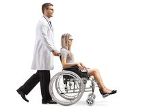 Young male doctor pushing a young woman in a wheelchair. Full length shot of a young male doctor pushing a young women in a wheelchair isolated on white stock photos