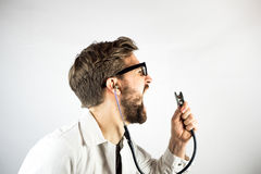 Young Male Doctor screaming at his stethoscope Royalty Free Stock Images