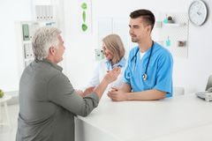 Young male doctor and senior female receptionist. Working with client in hospital stock photo