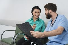 Doctor Showing X-ray To Happy Female Patient stock images