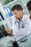 Young male doctor showing x-ray to patient. Doctor Royalty Free Stock Image
