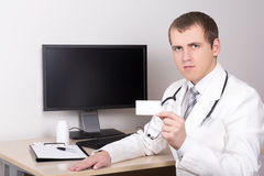 Young male doctor showing visiting card in office Stock Photo