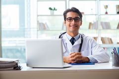 The young male doctor sitting at desk in hospital clinic. Young male doctor sitting at desk in hospital clinic Stock Photography