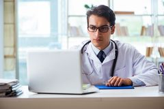 The young male doctor sitting at desk in hospital clinic. Young male doctor sitting at desk in hospital clinic Royalty Free Stock Image