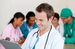 Young male Doctor Smiling at the camera. With his team in teh background Royalty Free Stock Photos