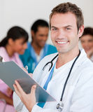 Young male Doctor Smiling at the camera. With his team in teh background Stock Photography