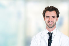 Young male doctor smiling standing in hospital hallway. Headshot portrait of friendly young male doctor smiling standing in hospital hallway clinic office Stock Photos