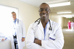 Young male doctor standing in hospital corridor, smiling, mature male doctor in background, portrait stock images