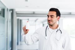 Young doctor holds blank bottle. Young male doctor while standing at hospital indoor holding in hand blank bottle Stock Image