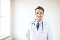 Young male doctor with stethoscope in hospital. Healthcare and medical concept - young male doctor with stethoscope in hospital Stock Photography