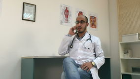 Young male doctor talking on mobile phone and looking at the watch. Professional shot on Lumix GH4 in 4K resolution. You can use it e.g. in your commercial stock footage