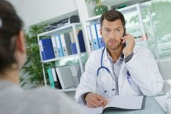 Young male doctor talking on phone in office. Young male doctor talking on the phone in office Stock Photos