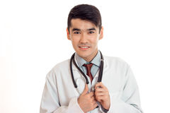 Young male doctor in uniform with stathoscope looking at the camera and smiling isolated on white background. Young male doctor in uniform with stathoscope Stock Image