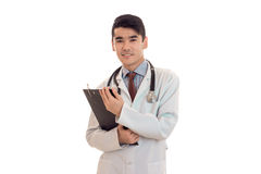 Young male doctor in uniform with stathoscope makes notes and smiling isolated on white background. Young male doctor in uniform with stathoscope makes notes and Royalty Free Stock Photo