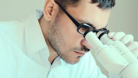 Young male doctor viewing through microscope. Closeup of young male doctor viewing through microscope stock video footage