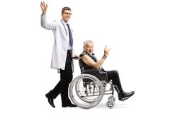 Young male doctor waving and pushing a mature male patient making a rock and roll hand sign in a wheelchair stock photography