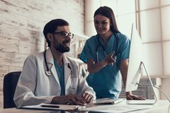 Young Male Doctor Working with Computer in Office. Nurse Standing Near. Male Laboratory Researcher Working with Graphs on His Personal Computer. Medicine Royalty Free Stock Images