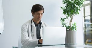 Young male doctor working on laptop 4k stock video footage