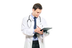 A young male doctor writing down notes Royalty Free Stock Photos