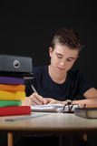 Young male doing his homework. Photo of a young teenager or student writing or doing his homework Stock Photography