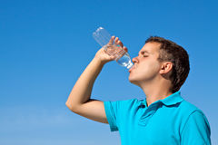 Young male drinking water. Against blue sky Royalty Free Stock Photography