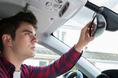 Young Male Driver In Car Checking Rear View Mirror Stock Image