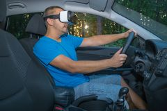 Man learning to drive with virtual reality glasses. Young male driver using virtual reality glasses in car interior Stock Images