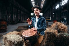Young male drummer against african wooden drum. Factory shop on background. Djembe, musical percussion instrument Stock Photo