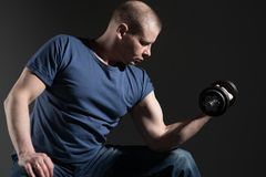 Young male dumbbell in his hands. Shakes his muscles. Studio stock photos