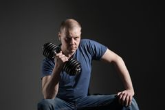 Young male dumbbell in his hands. Shakes his muscles. Studio royalty free stock photos