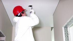 Young male electrician cutting holes in ceiling with handsaw stock video