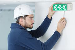 Young male electrician testing lighting sign. Male royalty free stock photo
