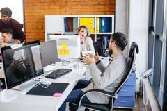 Young male employee is accompaning his speach with gestures. At workplace. chat among co-workers Stock Image