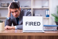The young male employee being fired from his work. Young male employee being fired from his work royalty free stock images