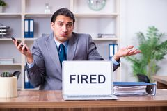 The young male employee being fired from his work. Young male employee being fired from his work royalty free stock photography