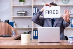 The young male employee being fired from his work. Young male employee being fired from his work royalty free stock image
