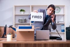 The young male employee being fired from his work. Young male employee being fired from his work stock image