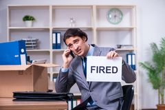 The young male employee being fired from his work. Young male employee being fired from his work stock photo