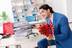 The young male employee with bunch of flowers in the office. Young male employee with bunch of flowers in the office royalty free stock photos