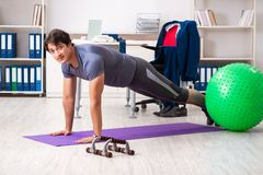 The young male employee exercising in the office royalty free stock photos