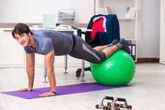 The young male employee exercising in the office royalty free stock photo