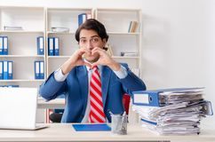 The young male employee in funny workaholic concept. Young male employee in funny workaholic concept royalty free stock photos