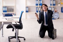 Young male employee in the office in time management concept stock photo