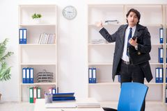 Young male employee in the office in time management concept stock images