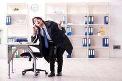 Young male employee in the office in time management concept royalty free stock photography