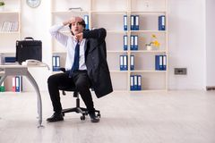 Young male employee in the office in time management concept stock photography