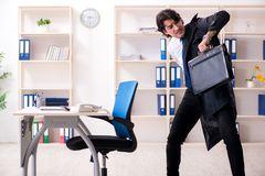 Young male employee in the office in time management concept stock image