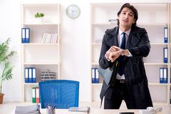 The young male employee in the office in time management concept stock image