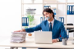 Young male employee with tape on the mouth. The young male employee with tape on the mouth stock photo