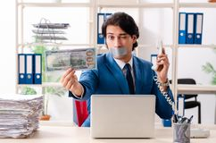 Young male employee with tape on the mouth. The young male employee with tape on the mouth royalty free stock photo